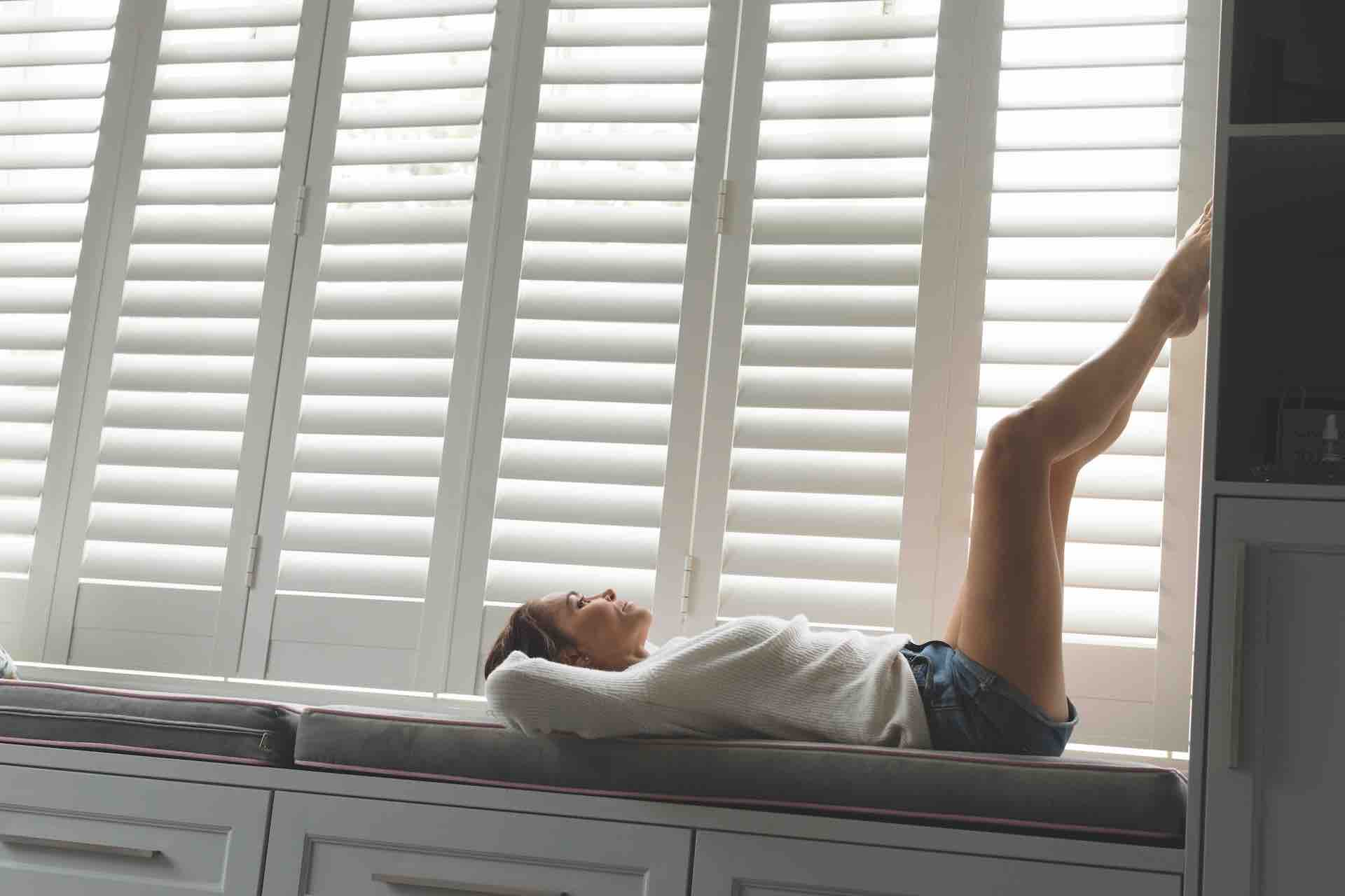 how to deal with toxic family when you are stuck together blog header image - girl laying on window seat with feet up