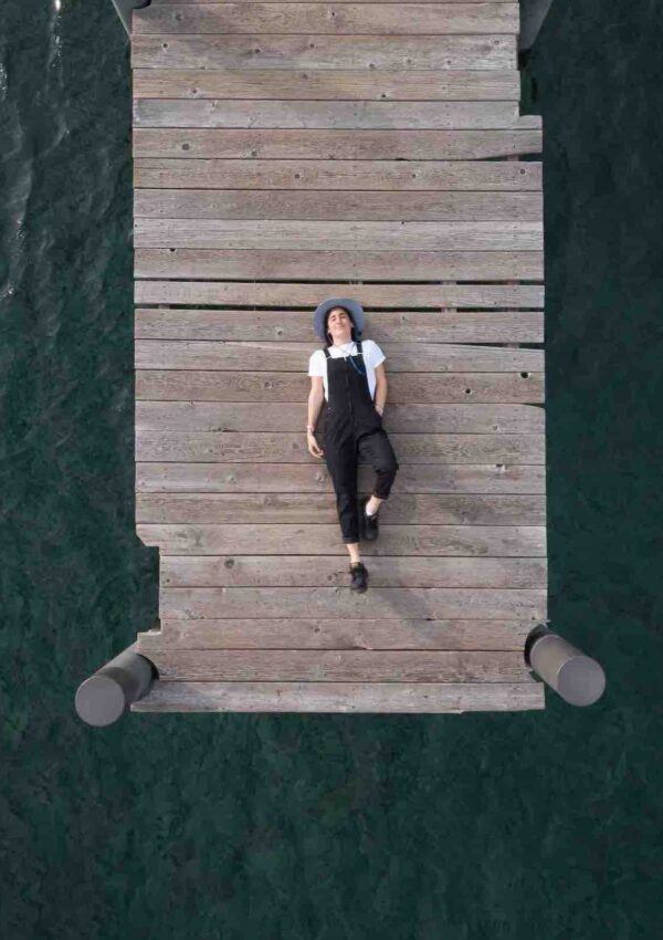 woman laying on dock surrounded by water