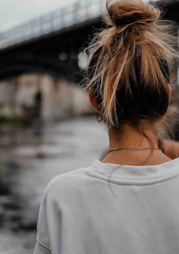 back portrait of a blonde girl standing in front of a bridge